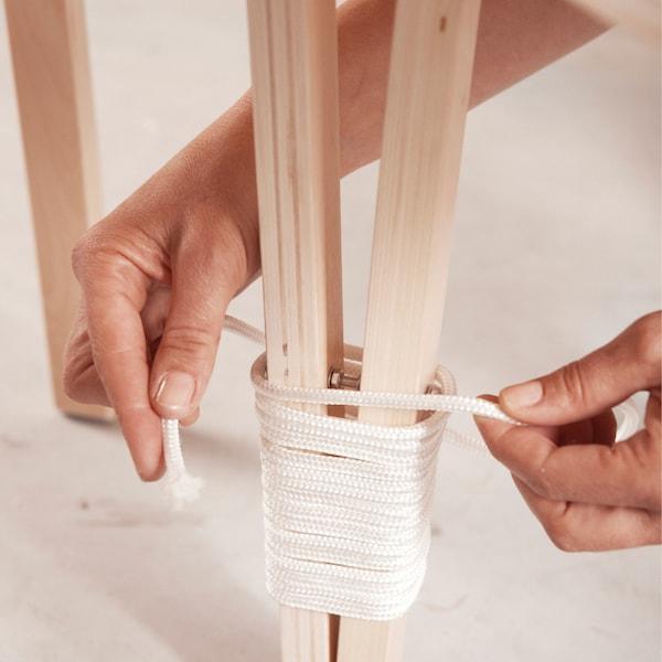 De bas en haut, entourez les pieds avec un fil de nylon plus épais afin de dissimuler les écrous.