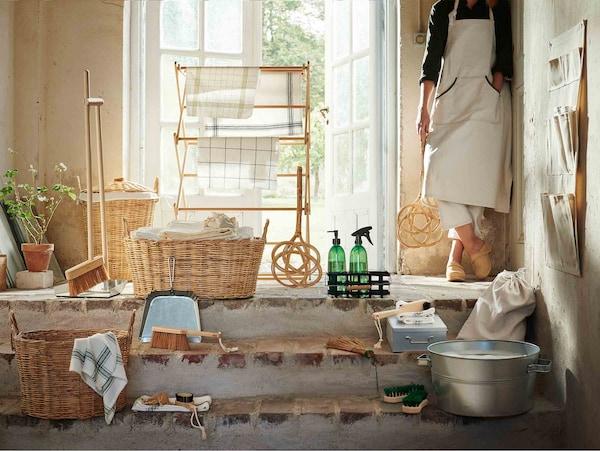 De BORSTAD collectie gepresenteerd in een zonovergoten deuropening, terwijl een vrouw met een mattenklopper in haar hand op het vloerkleed staat.