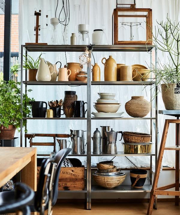 De la poterie et des ustensiles de cuisine exposés sur de grande étagères en métal.