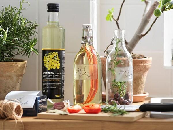 De l'huile de canola biologique SMAKRIK et deux bouteilles avec bouchon KORKEN sont sur un comptoir de cuisine à côté d'une planche à découper.