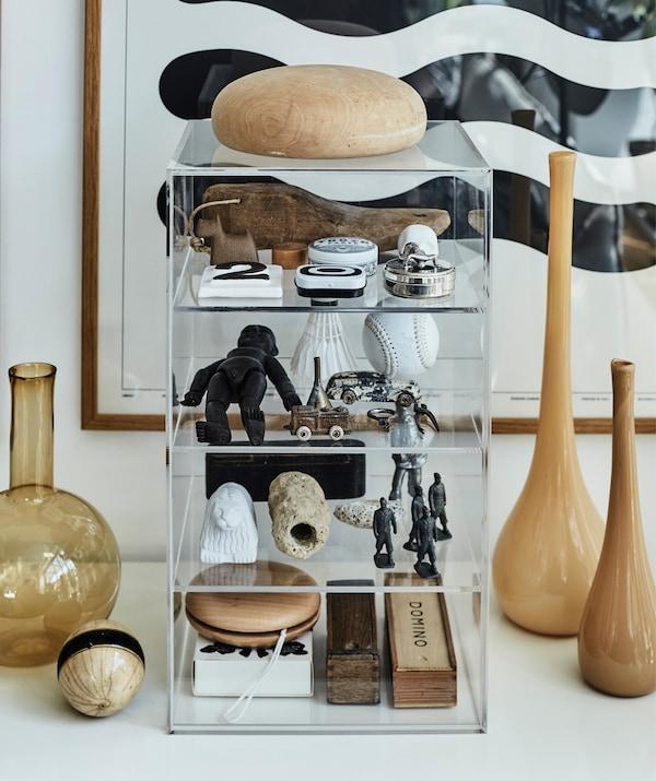 De vieux jouets rangés dans un caisson à tiroirs transparent à côté de vases en verre brun.