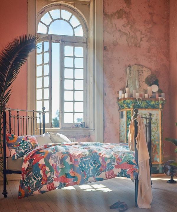 De zon schijnt binnen in een slaapkamer via een groot gebogen venster. Een bed met een fijn metalen bedframe is opgemaakt met SKOGSFIBBLA bedtextiel.