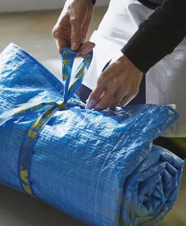 Image of a blue picnic blanket made from FRAKTA blue bags and tea towels rolled up and tied using the handles from the bag