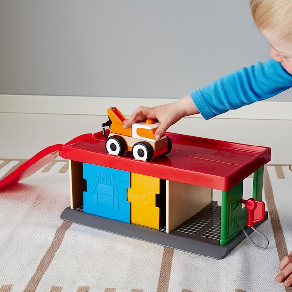 A toddler playing with the multicolored IKEA LILLABO garage with a tow truck on the floor.