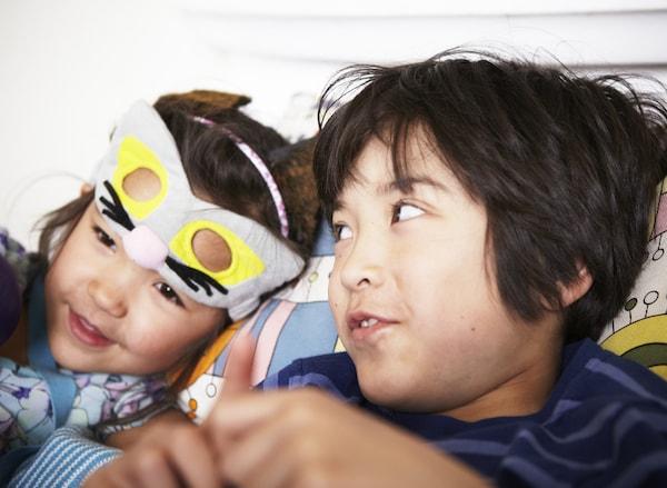 Dečak i devojčica s maskom u obliku mačke, sede udobno na sofi i pričaju.