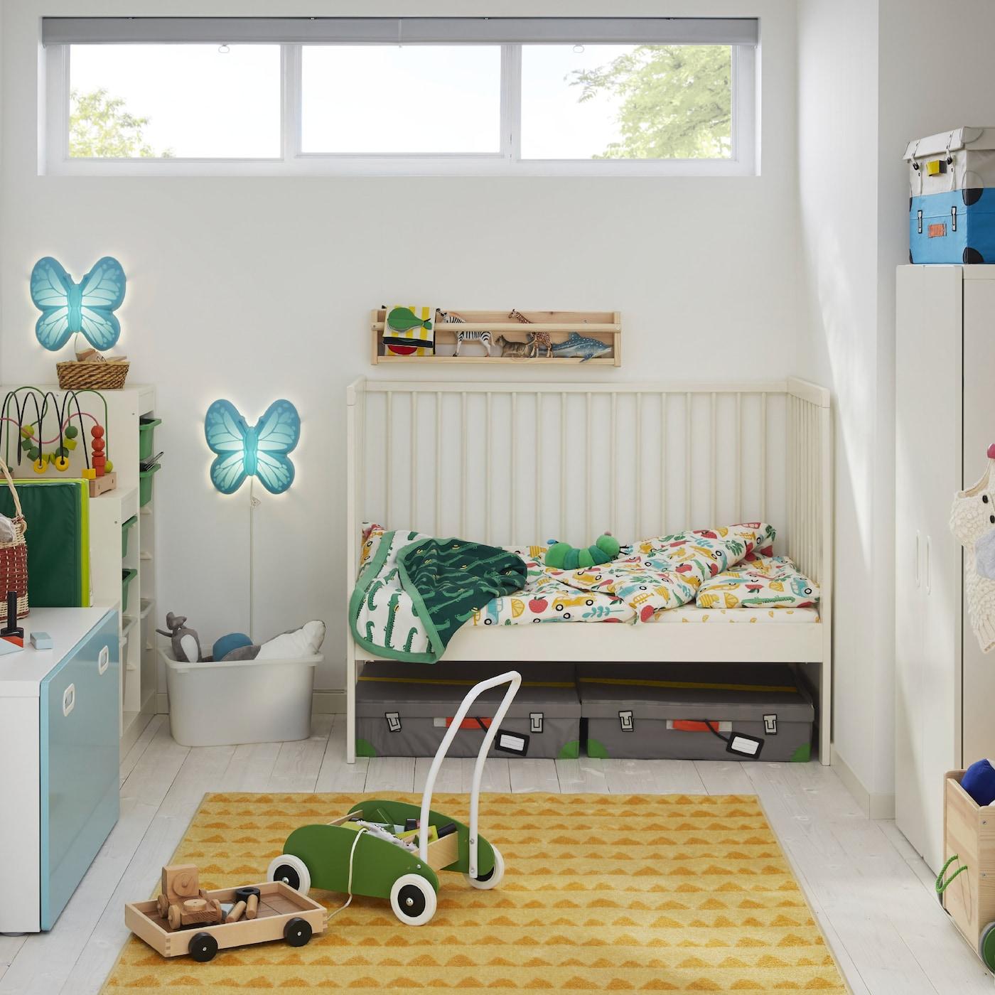 Dečja soba s belim krevecem, žutim tepihom, belim garderoberom, zelenim kamiončićem i zidnim lampama u obliku leptira.