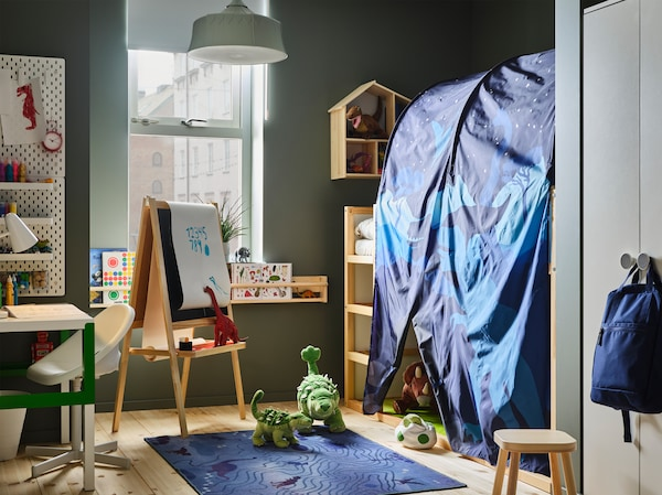 Dečja soba s plavim šatorskim krilom za krevet, plišanim dinosaurusima, belim/zelenim pisaćim stolom, svetlozelenom visilicom i plavim tepihom.