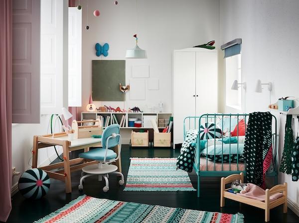 Dečja soba sa šarenim tepisima, krevetnim okvirom u tirkiznoj boji, belim garderoberom, roze zavesama i dečjim radnim stolom.