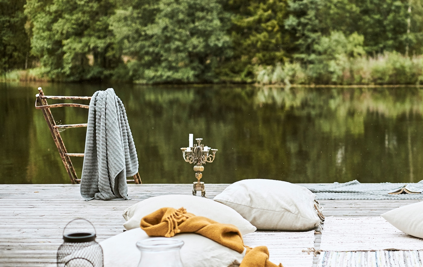 Decking by a lake, cushions and rugs on the floor Bedouin-style, a grey towel hangs on rusted steps next to a candelabra.