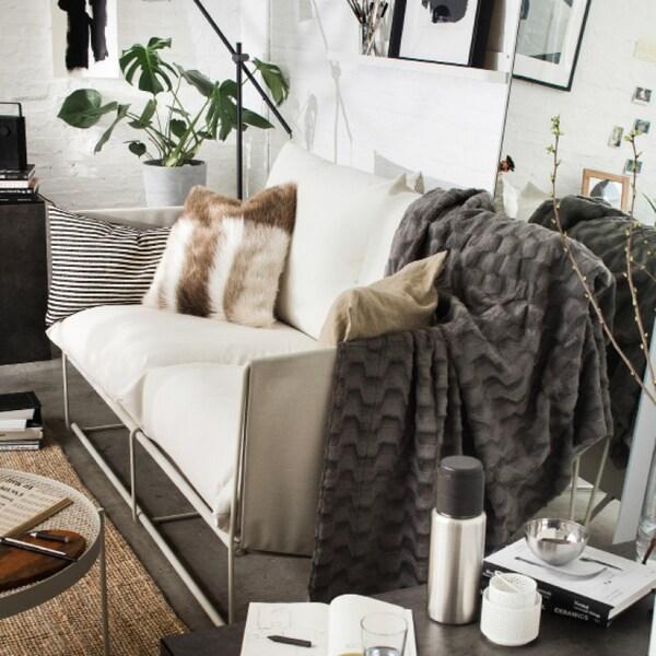 Déco de salon chaleureuse avec canapé, coussins, couvertures et plantes