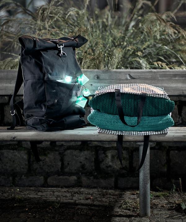 Décor de soirée avec un banc public sur lequel sont placés un sac à dos avec une guirlande lumineuse allumée sortant de ses poches et un sac avec des textiles.