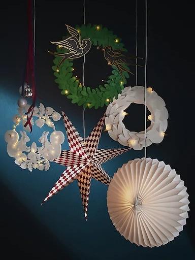 Decoraciones de papel de Navidad y farolillos colgados frente a un fondo azul oscuro.