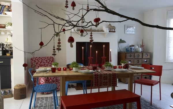 Decorations hang from a branch over a nature-inspired festive dining room table.