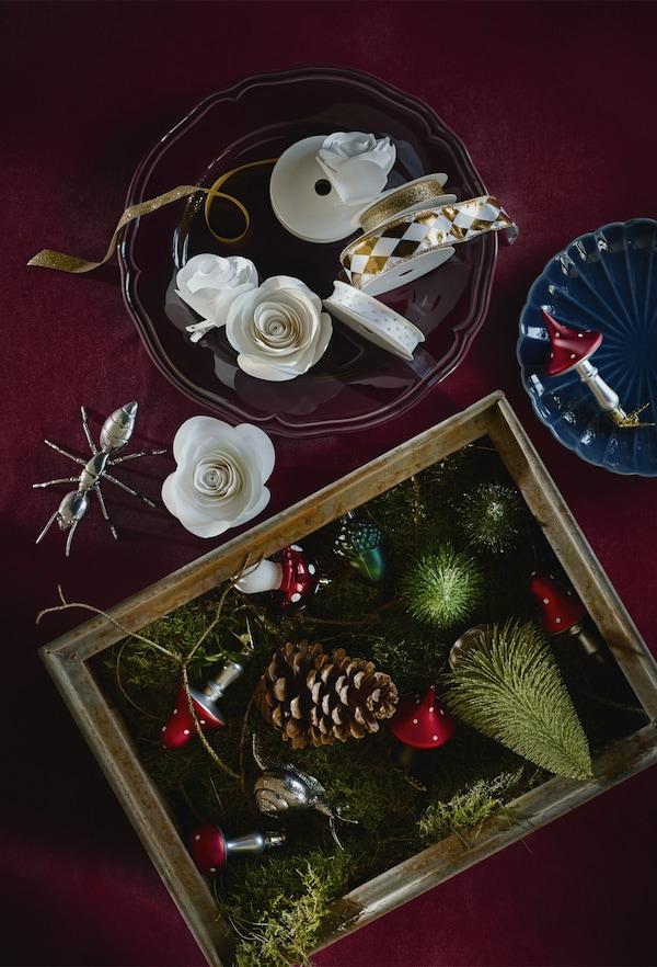 Decorațiuni de pom și panglică în boluri și cutii așezate pe masă.
