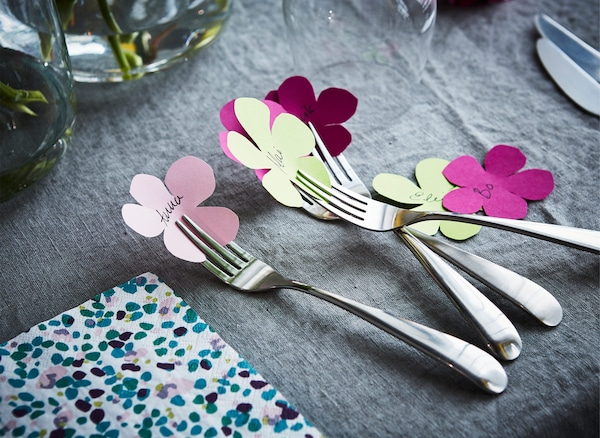 Decorative homemade place cards, shaped as flowers, next to cutlery on a dining table.