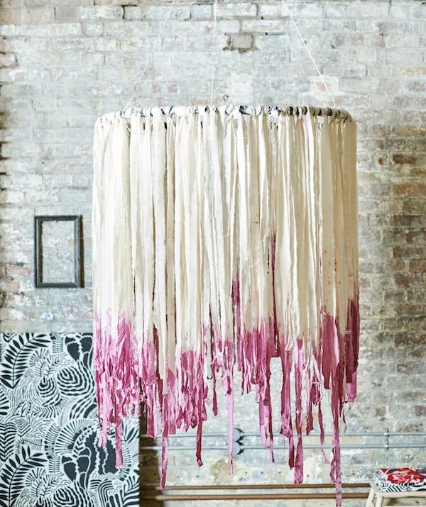 Decorazione boho appesa accanto a una parete in mattoni. Al cerchio sono legate delle strisce effetto nappina di tessuto bianco, tinte di rosa alle estremità - IKEA