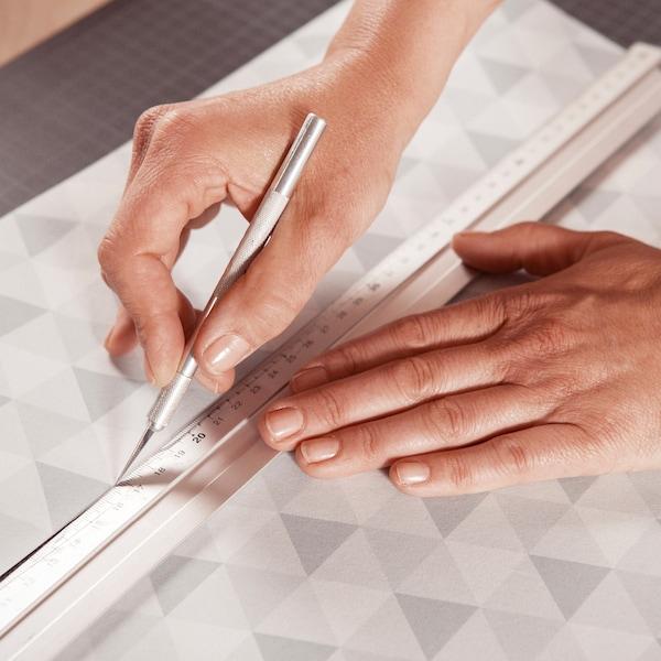 Découpez le papier peint pour les tiroirs.