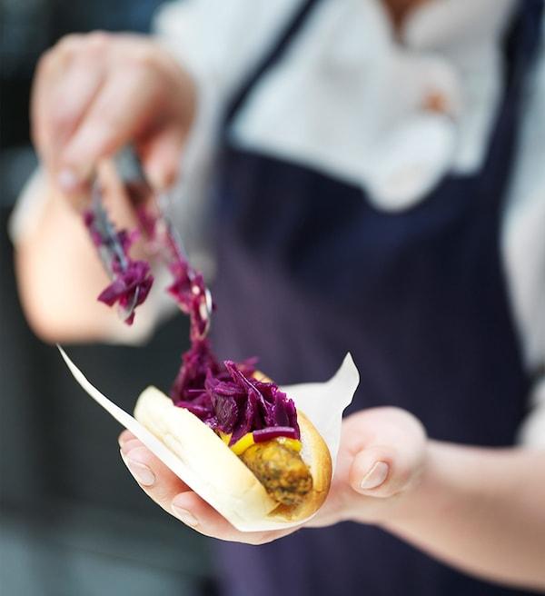 植物性食品でできたイケアのベジドッグに赤キャベツをトッピングしているイケアビストロのコワーカーのクローズアップ。