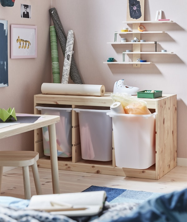 Deep storage bins in a light wood unit, with art supplies and shelves above.