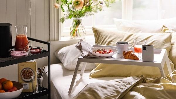 Déjeuner servi sur un plateau blanc KLIPSK sur un lit avec du linge de lit ÄNGSLILJA, avec plus de nourriture sur une desserte.