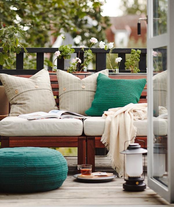 Déjeuner sur le balcon avec portes ouvertes et plusieurs coussins, couvertures et meubles d'extérieur.