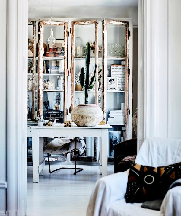 Декоративные предметы и банки в белом шкафу-витрине за белым письменным столом.