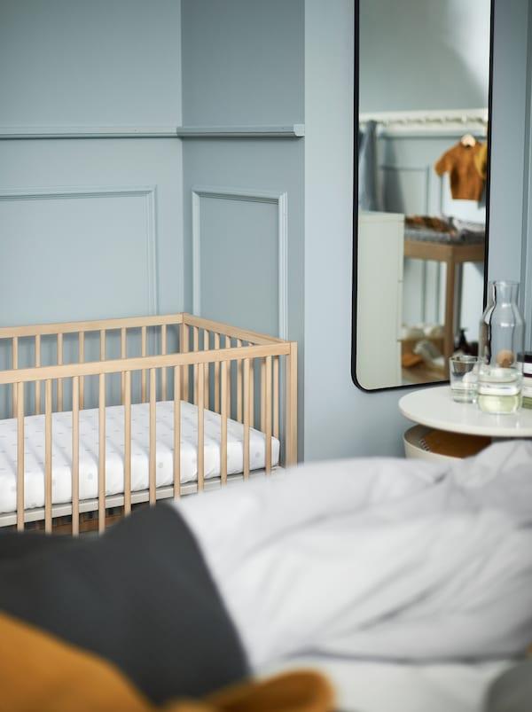Del af et lyseblåt soveværelse med et hvidt sengebord, et spejl og en SNIGLAR tremmeseng af træ.