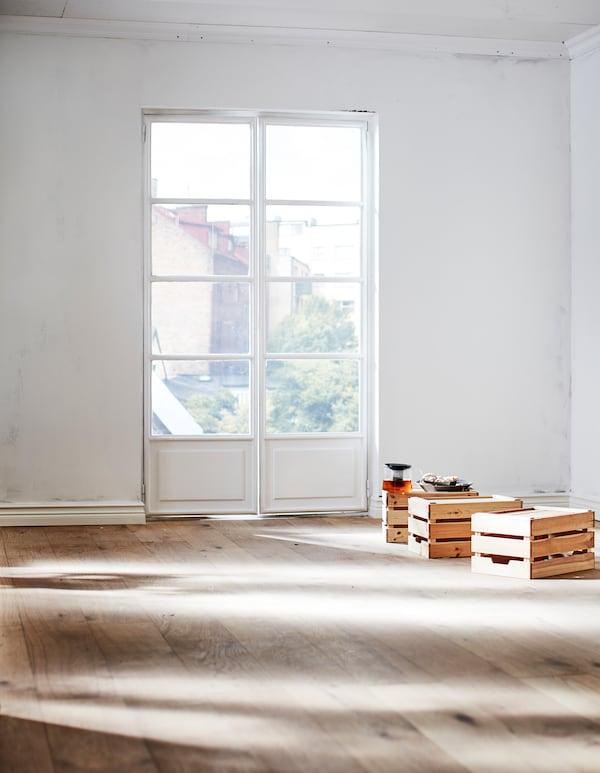 Del af et tomt rum med en hvid, umalet væg og et gulv af naturligt træ. Sollyset falder ind gennem franske døre.