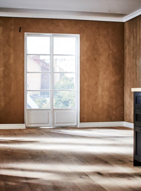 Del af et tomt rum med franske døre, trægulv og væggen malet i en varm brun nuance med en faux finish-teknik, så den får et ruskindlook.