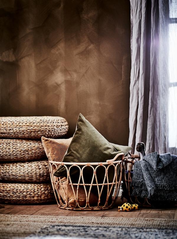 Del af soveværelse i jordbrune nuancer. SNIDAD kurve af rotting med tekstiler, ALSEDA taburetter og tæpper af naturmaterialer.