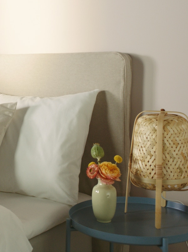 Del av sängkant och sängbord syns med liten vas och nattlampa.