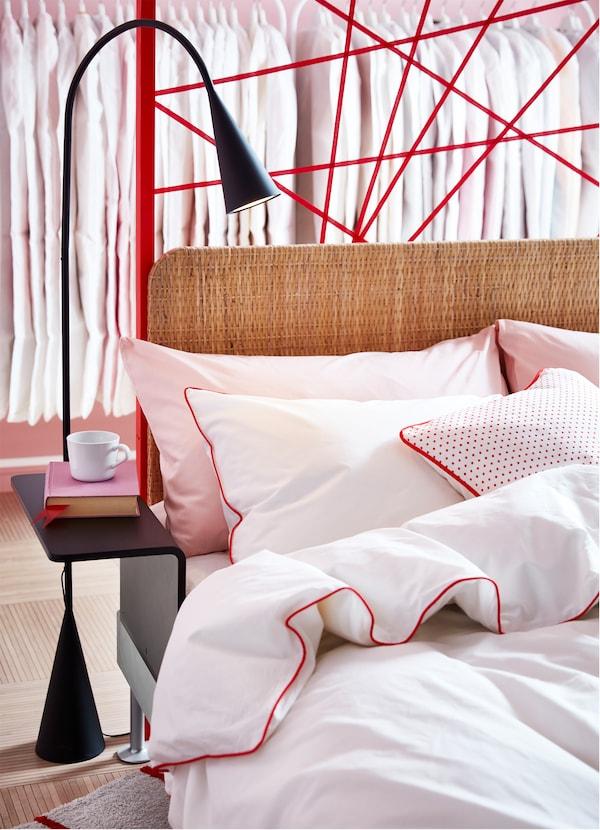 DELAKTIG هيكل سرير مع لوح رأس إضافي من الروطان ومصباح قائم أسود مع طاولة جانبية.