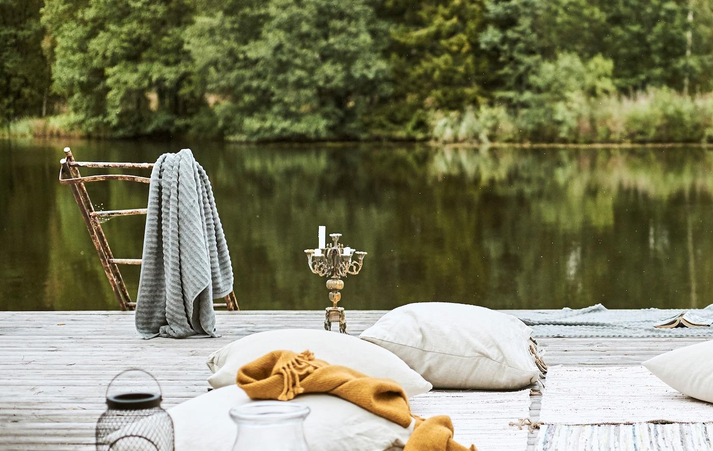 Deque à beira de um lago, almofadas e tapetes sobre o chão ao estilo beduíno, uma toalha cinzenta pendurada numas escadas enferrujadas ao lado de um candelabro.
