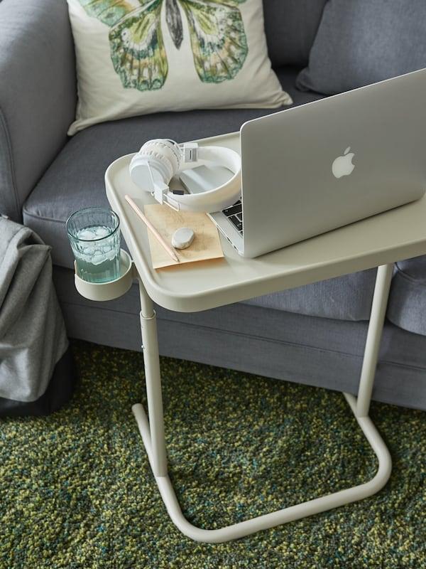 Der BJÖRKASEN Laptoptisch mit Getränkehalter steht vor einem Sofa.