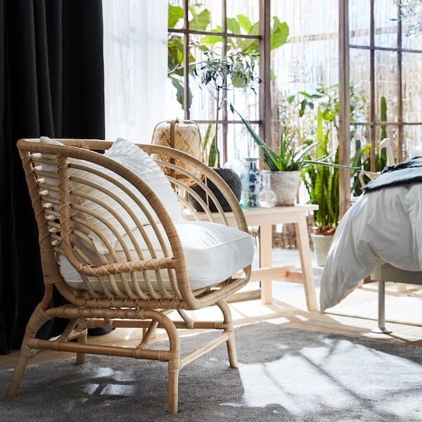 Der BUSKBO Sessel aus Rattan mit weissen Polstern an einer Balkontür