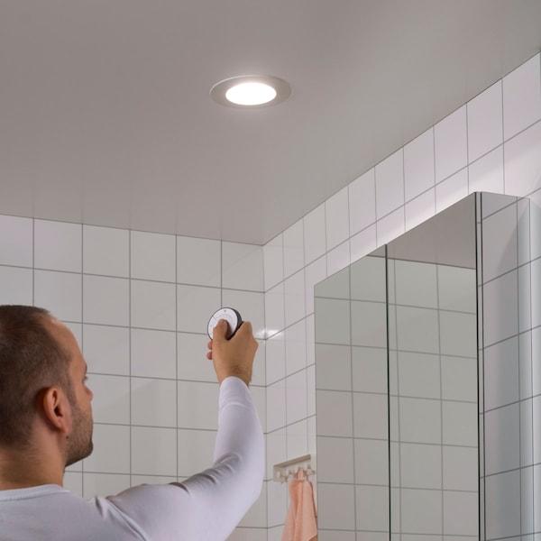 Der Einbauspot hängt an der Decke eines weiß gekachelten Bades und wird miteiner Fernbedienung bedient.