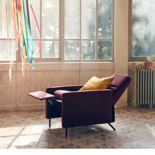 Der neue GISTAD Ruhesessel in Dunkelrot in Liegeposition in der Mitte eines Raumes