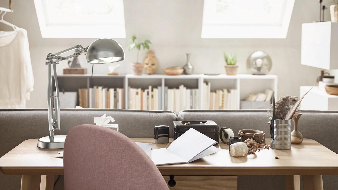Derrière un canapé, un bureau LISABO en placage de chêne, une lampe de travail FORSÅ et une chaise pivotante forment un espace de bureau à domicile.