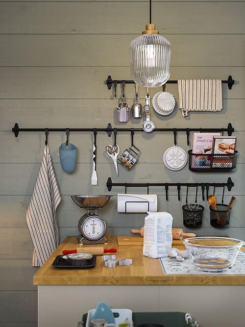 Des accessoires de cuisine sur un îlot d'inspiration rustique française et, sur un mur de bois vert, des barres-supports noires et des crochets sur lesquels sont suspendus des ustensiles.