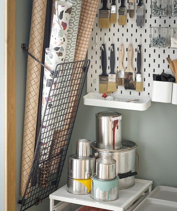 Des accessoires de loisir rangés de différentes façons; des rouleaux de papier peint dans un support, des pots de peinture empilés et des pinceaux accrochés à un panneau perforé.