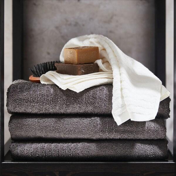 Des accessoires de salle de bains empilés sur des serviettes de bain VÅGSJÖN gris foncé pliées.