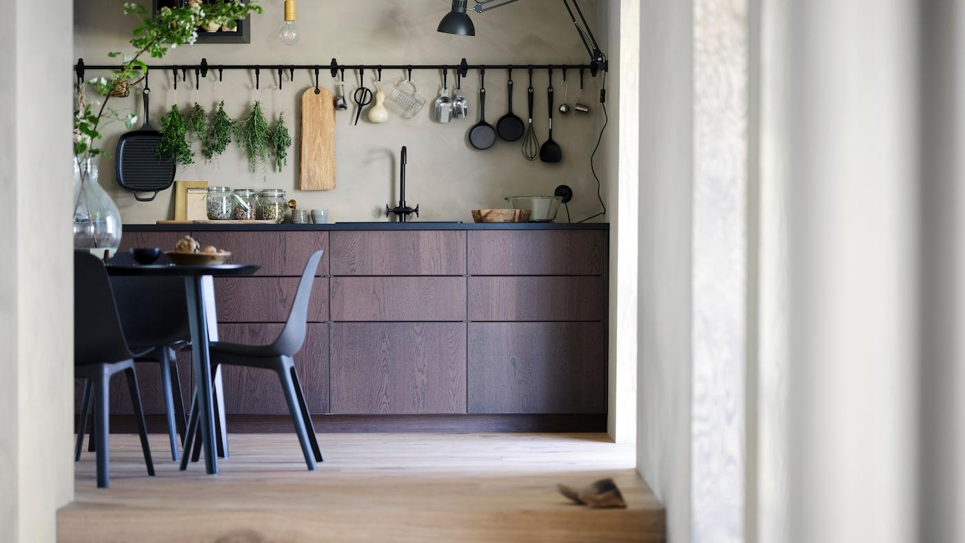Des armoires de cuisine en bois foncé couvrent la partie inférieure d'un mur de cuisine. Des ustensiles de cuisine sont suspendus au-dessus des armoires.