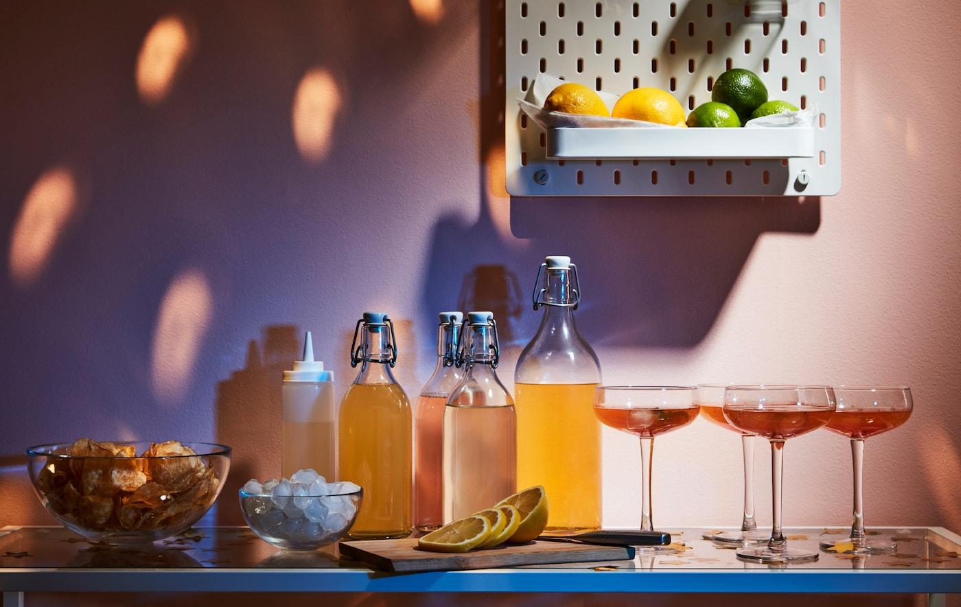 Des boissons, verres et accessoires sur une table basse. Sur le mur au-dessus, des citrons jaunes et verts sont présentés sur un panneau perforé SKÅDIS.
