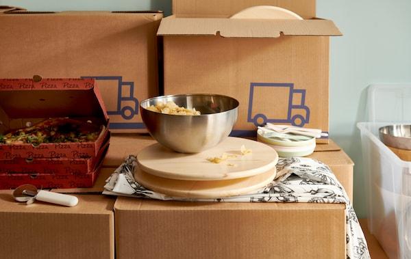 Des boîtes de pizza et un plateau pivotant avec des en-cas dans un saladier BLANDA BLANK sur une pile de cartons d'emballage JÄTTENE.