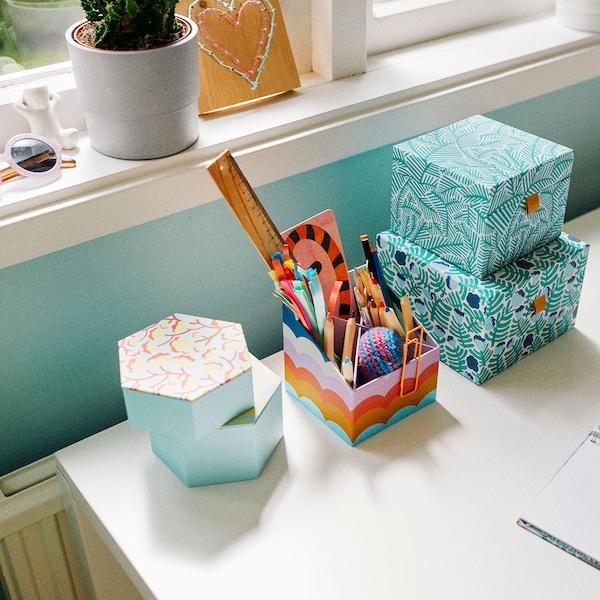 Des boîtes de rangement colorées pour papeterie sur un bureau blanc près d'une fenêtre.