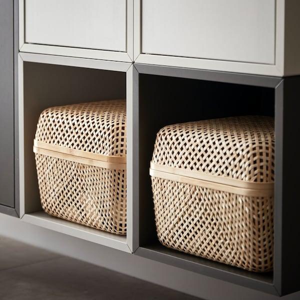 Des boîtes de rangement SMARRA naturelles avec couvercles placées dans une étagère murale.
