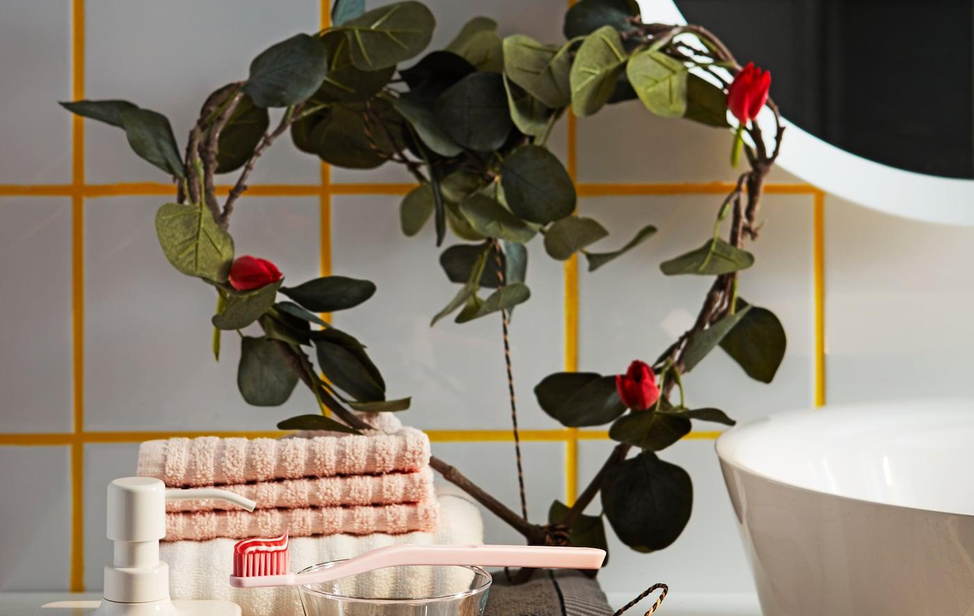Des branches de feuilles artificielles d'eucalyptus vert IKEA SMYCKA en forme de cœur décorent une étagère de salle de bain.
