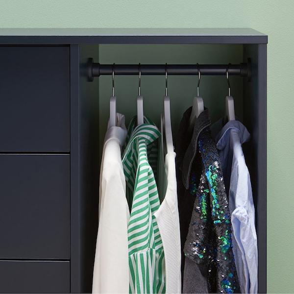 Des chemises suspendues à une barre à l'intérieur d'un meuble de rangement bleu-noir.