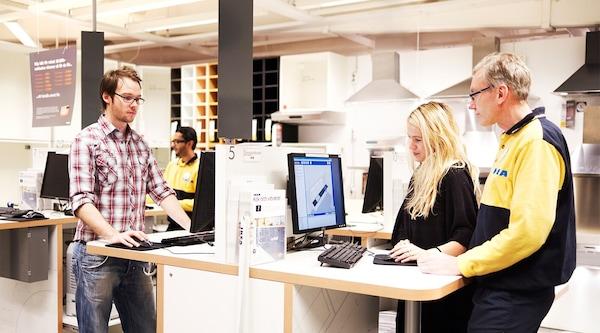 Des clients qui utilisent les kiosques de planification de cuisine au magasin IKEA.