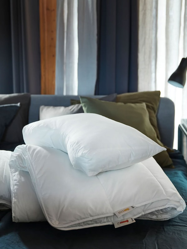 Des couettes et des oreillers sont empilés sur le lit.